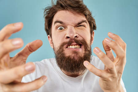 Bearded man in white T-shirt emotions gestures with hands displeased facial expression blue background