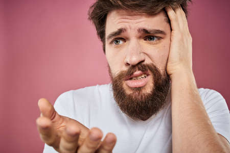 bearded man in white t-shirt emotions displeased facial expression studio pink background