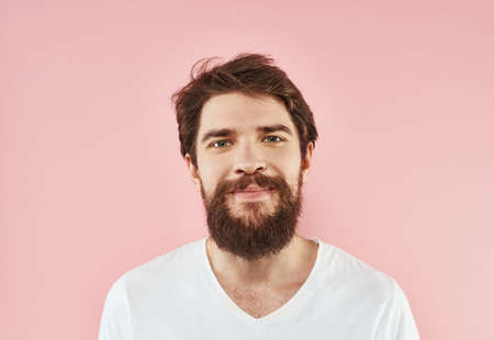 Portrait of a young man with a beard in a white T-shirt on a pink background