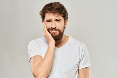 A man in a white t-shirt with a beard emotions displeased facial expression light background