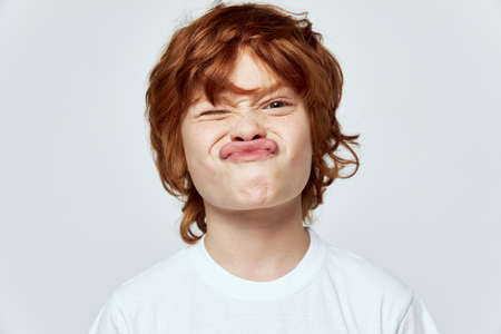 Grimacing boy face close-up cropped view white t-shirt studio