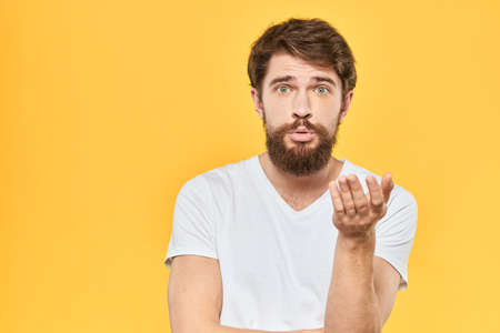 Bearded man in a white T-shirt gestures with his hands emotions studio yellow background