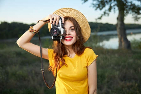 Woman holding camera looks into the camera lens red lips hat nature