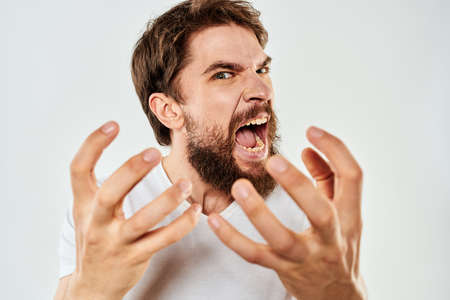Emotional bearded man in a white t-shirt gestures with his hands light background Archivio Fotografico