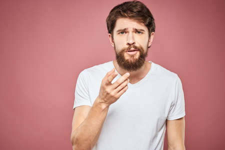 emotional man white t shirt sad facial expression pink background