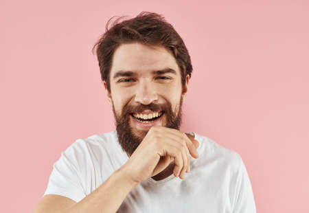 Portrait of a man with a beard and mustache on a pink background close-up cropped view