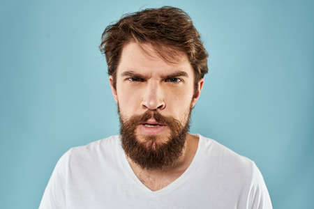 Bearded man emotions facial expression gestures hands close-up blue background