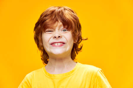 Red-haired child grimaces yellow T-shirt