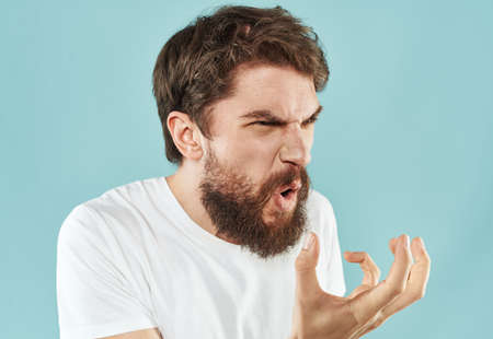 Emotional bearded man on a blue background cropped view of gesticulating with his hands Imagens