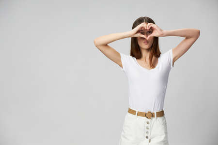 A woman in a white t-shirt holds her hands in the form of a heart in front of her eyes and cropped view Reklamní fotografie
