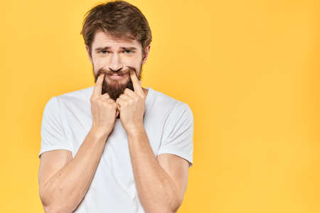 Bearded man emotions gestures with hands facial expression white t-shirt yellow background