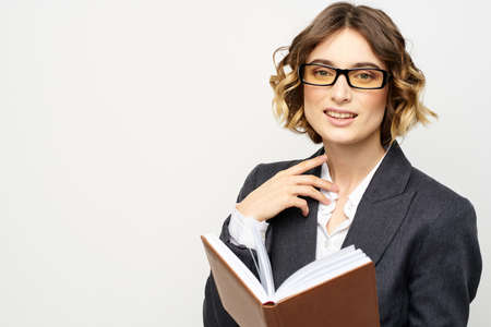 Woman at work with book in hand light background classic suit glasses head 版權商用圖片