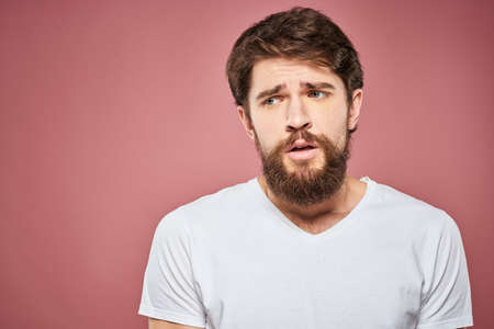 Emotional bearded man in white T-shirt discontent pink background Zdjęcie Seryjne