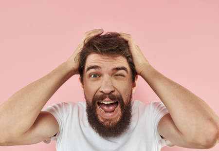 Portrait of an energetic guy on a pink background in a white t-shirt cropped view Zdjęcie Seryjne