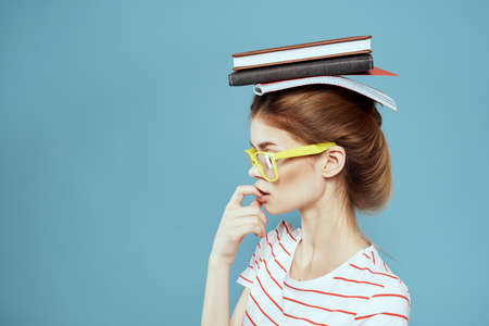 Female student with books on her head and in yellow glasses on a blue background cropped view