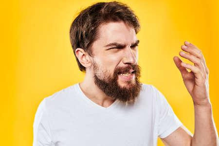 bearded man gesturing with hands studio lifestyle discontent yellow background Zdjęcie Seryjne