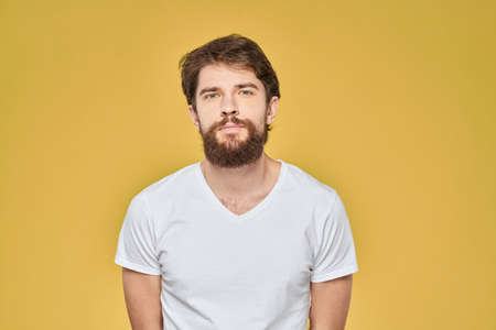 Bearded man on emotions white t-shirt fun lifestyle yellow background