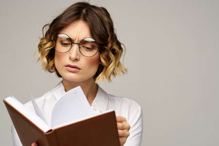 Business woman with notepad and glasses on a light background hairstyle success emotions 版權商用圖片