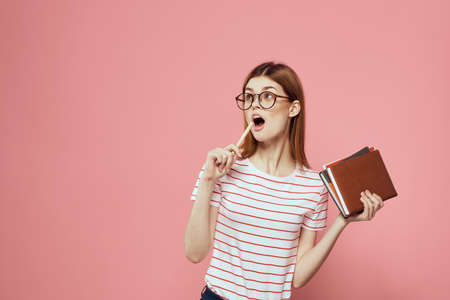 female student with notepads on pink background gesturing with her hands glasses on her face striped t-shirt model