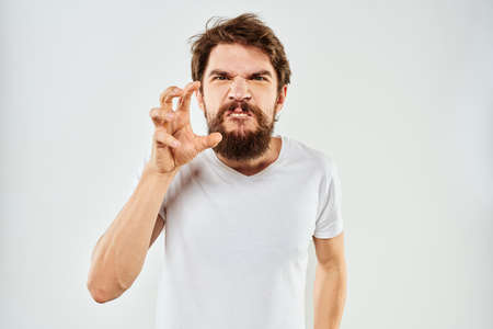 Emotional bearded man in a white t-shirt gestures with his hands light background Zdjęcie Seryjne
