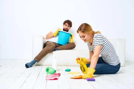 A man sits on a sofa with a bucket of a woman on the floor with a detergent for kitchen interior chores 免版税图像