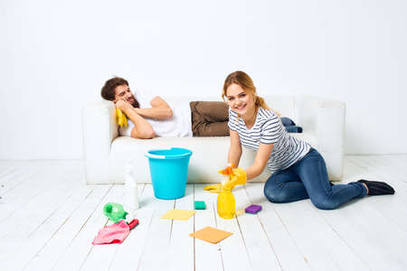 young couple at home near sofa washing supplies cleaning lifestyle