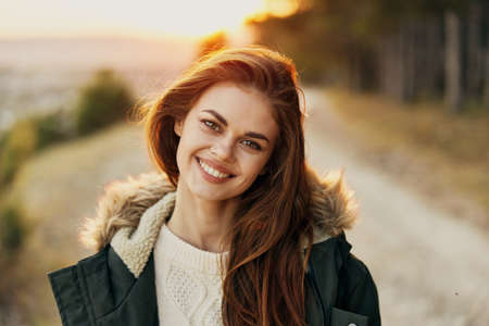 Smiling woman warm jacket Autumn forest in the background close-up