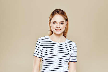 Cheerful woman striped t-shirt studio beige background lifestyle emotions Stock fotó