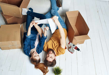 A man and a woman with boxes are moving. Well, an apartment is being renovated by a family Foto de archivo