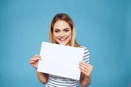 Emotional woman holding a sheet of paper in her hands lifestyle close-up blue background Copy Space