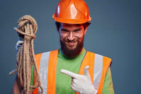 Emotional man in work uniform orange helmet rope professional