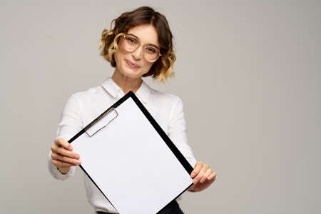Business woman in a light shirt and a folder with documents in hands cropped view of work