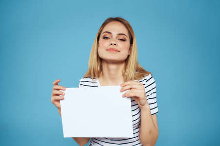 Woman holding sheet of paper striped T-shirt Copy Space cropped view blue background