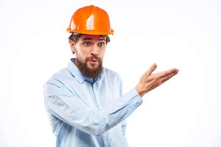 A man in an orange helmet shirt construction industry worked light background