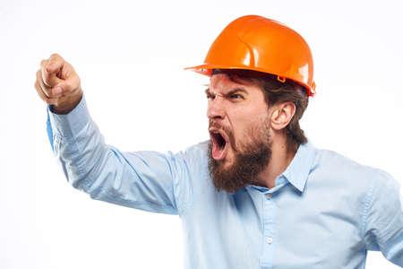 Angry man in orange hard hat industry work dissatisfaction cropped view Foto de archivo