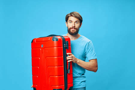 Traveler with a red suitcase blue t-shirt isolated background mustache