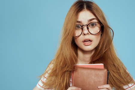 energetic female student with notepads and glasses model blue background Stok Fotoğraf