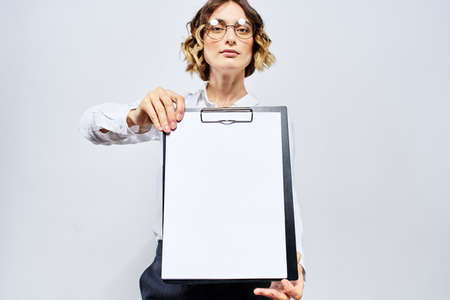 Business woman with a folder of white documents in her hand on a light background And hairstyle glasses model