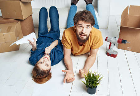 To women men on a wooden floor with boxes and a flower in a pot Foto de archivo