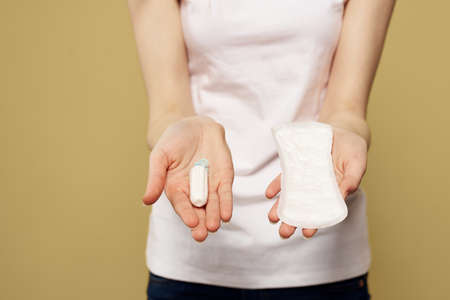 Girl with a tampon and a pad in her hand on a beige background white t-shirt cropped view