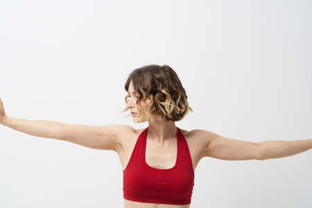 the girl is engaged in yoga on a light background Red T-shirt gesticulating with his hands