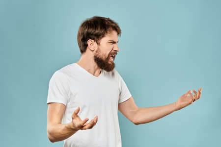 Man gestures with his hands emotions displeasure white t-shirt blue background