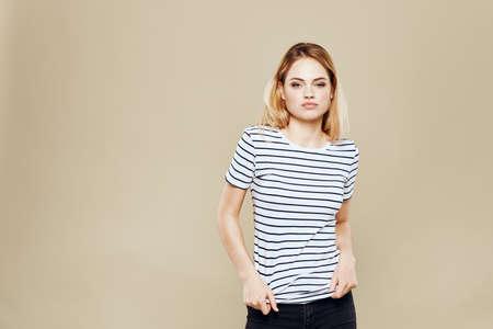 Cheerful woman striped t-shirt studio beige background lifestyle emotions Stockfoto