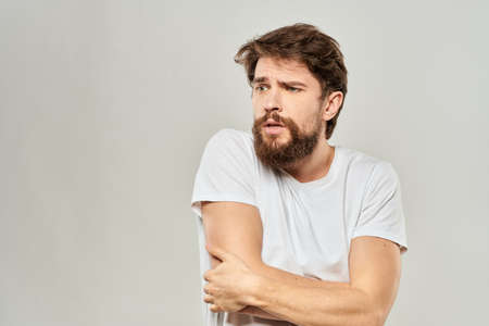 man in white t-shirt gesturing with his hands studio dissatisfaction lifestyle light background