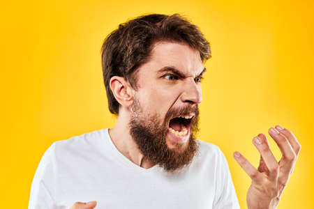 emotional bearded man gesturing with hands aggression discontent close-up yellow background
