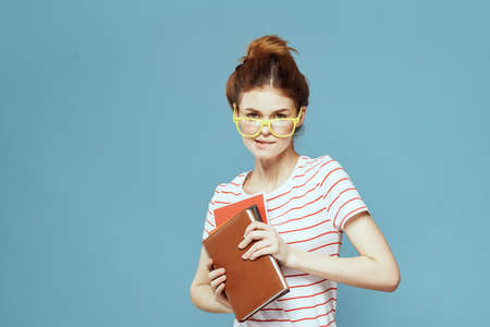 Female student with books in hands on a blue background and yellow glasses model hairstyle cropped view