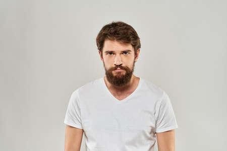 Bearded man gesturing with hand white cropped t-shirt studio lifestyle Standard-Bild