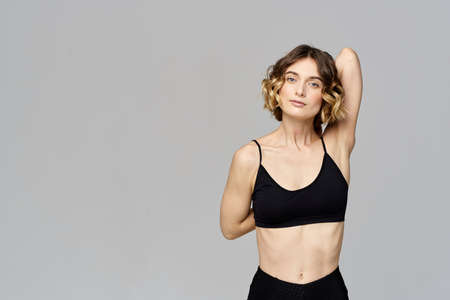 woman in short t-shirt goes in for sports on a gray background exercise exercise copy space