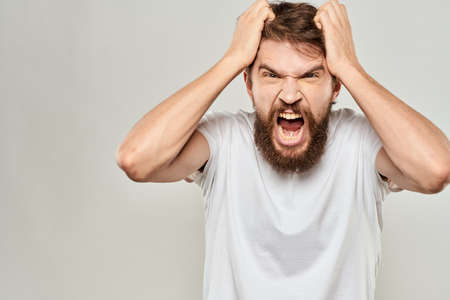 bearded man gesturing with his hands in a white t-shirt aggression light background Foto de archivo