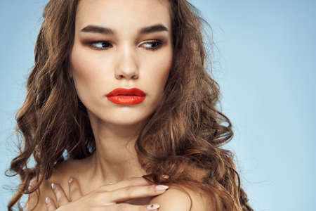 Brunette naked shoulders red lips fashionable hairstyle blue background
